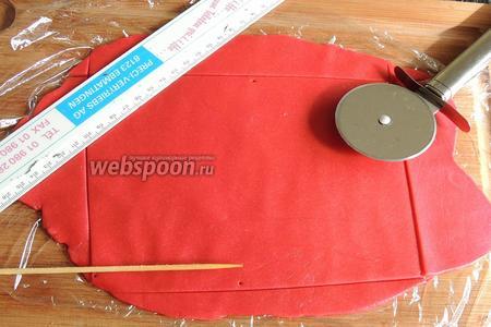 Формируем коровку. Красный марципан раскатываем скалкой между 2 пищевыми плёнками. Отмеряем линейкой, чтобы длина и ширина соответствовали. Вырезаем из марципана четырёхугольник.