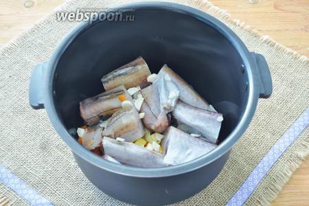 В чашу мультиварки выложим рыбу. Посыпем чесноком, солью и перцем.