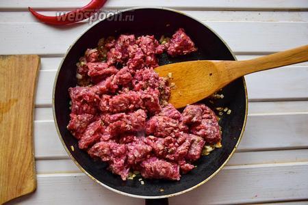 Нагреем сковороду с 2 столовыми ложками масла, выложим фарш и обжарим на среднем огне до полуготовности.
