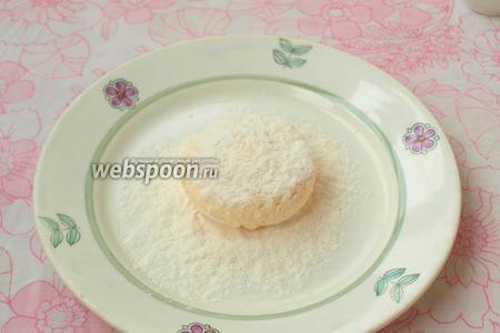 На тарелку насыпать муку, положить сырник и присыпать мукой сверху.