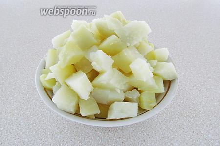 Картофель в кожуре залить горячей, подсоленной водой и отварить до мягкости, а затем хорошо остудить, почистить и нарезать кубиками.