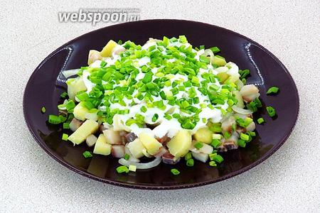 Массу выложить на сервировочную тарелку, полить сверху сметаной и обильно посыпать зелёным луком.