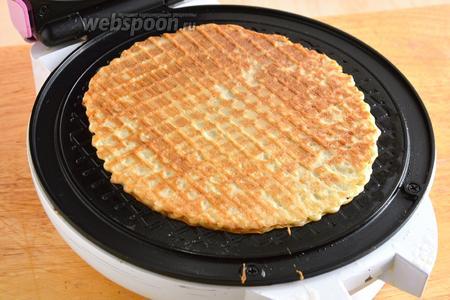Горячие, только что выпеченные вафли, сразу же снимайте лопаточкой на тарелку и скручивайте в трубочки.