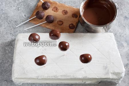 Охлаждённые кейк попсы обмакиваем в растопленный на водяной бане чёрный шоколад.