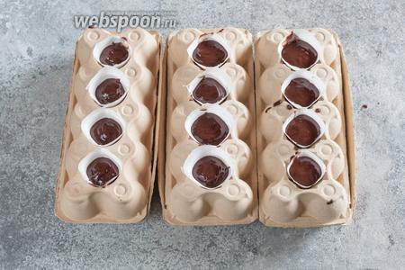 Заливаем шоколад в стоящие в яичных решётках бумажные конусы. У вас должно остаться ещё 2-3 столовые ложки шоколада.