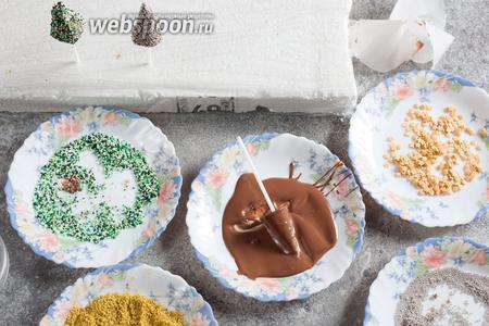 Растапливаем оставшийся шоколад и выливаем его на предварительно разогретую тарелку. Снимаем с каждого конуса бумагу и покрываем его жидким шоколадом, катая по тарелке. Теперь о свойствах разных декоров. Проще всего получалось с фисташковой мукой: в ней смазанный шоколадом конус нужно просто обвалять, садится отлично! С кондитерскими бусинами дела обстоят хуже. Звёздочками реально только обсыпать сверху, валять в них бессмысленно. Те звездочки, которые коснулись шоколада, но не приклеились, падают вниз грязными. В мелких бусинках можно валять, а можно обсыпать. И в том, и в другом случае поверхность покрывается неравномерно, и остаются испачканные шоколадом отходы. В общем, мой фаворит — фисташки! Они, кстати, по-моему, и вкуснее. С бусинами — это я для детей.