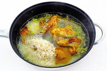 Рис тщательно промыть до полного исчезновения мути и выложить к крылышкам. Смесь посолить по вкусу или посыпать овощной приправой, добавить оставшуюся приправу «карри» и влить горячую воду.