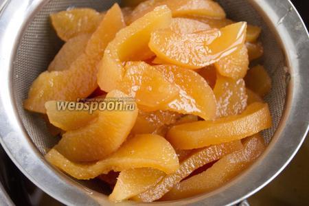 Добавьте оставшийся сахар. Повторите процесс «нагреть-остудить» от 3 до 5 раз. Добавьте лимонную кислоту при последней варке. Цукаты выложите в ситечко. Дайте стечь сиропу.