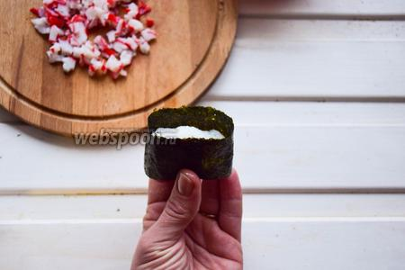 Далее оборачиваем наш брусочек нарезанным листом нори. Края смачиваем и приклеиваем друг к другу. У вас должна получится так называемая «ванночка», куда ещё может поместиться начинка.