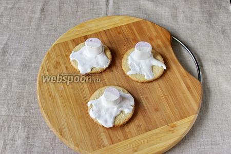 Наносим на печенье белковый крем, неравномерно, будто бы растаял снег, затем делаем голову снеговика с помощью зефира маршмеллоу.