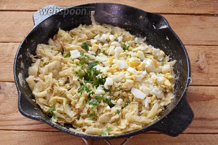 В самом конце добавьте к капусте соль и перец по вкусу. Можно добавить зелень (опционно). Отварите куриные яйца до готовности. Очистите их и измельчите. Добавьте к капусте. Перемешайте. Начинка готова.