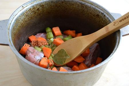Налейте в казан или толстостенную посуду оливковое масло, добавьте кусочки кролика, кусочки лука, моркови и сельдерея. Посолите, поперчите, добавьте лавровый лист.