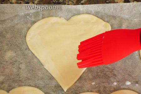 Тесто тонко раскатать. Формочками вырезать 14 сердечек. Края 7-и сердечек смазать молоком.
