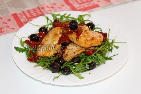 Выкладываем куриное филе, маслины и томаты поверх рукколы и поливаем соусом из сковороды.