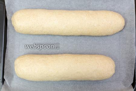 Выкладываем тесто на рабочую поверхность и делим на 2 части. Из каждой формируем либо батоны, как у меня, либо круглый хлеб. Накроем полотенцем и дадим им отдохнуть минут 20.