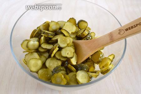 Нарежьте маринованные огурчики тонкими кружочками.