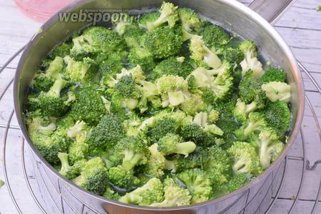 Добавим к картофелю поделенную на соцветия капусту брокколи. Бланшируем ещё около 2 минут. Затем овощи вынимаем и отрушиваем от воды.