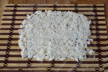 Макису застилаем пищевой плёнкой. На плёнку выкладываем рис.