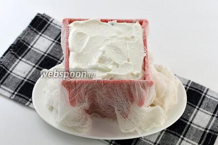 Специальную форму для пасхи выложить чистой влажной марлей. Следите, чтобы внутри не образовывались складки. Под форму выложить тарелку, в которую будет стекать жидкость. Заполнить форму поочерёдно ванильной и тыквенной творожными массами.