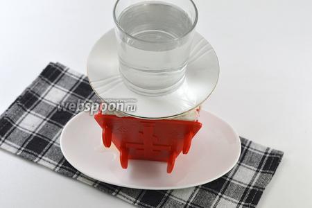 Завернуть концы марли наверх. Сверху на марлю выложить небольшое блюдце и груз (стакан или банку с водой). Поставить пасху в холодильник, минимум на 12 часов. Периодически сливать образующуюся внизу жидкость.