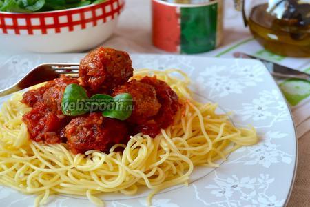 Разложить спагетти по тарелкам, распределив сверху пасты соус с тефтельками. Украсить листиками базилика.