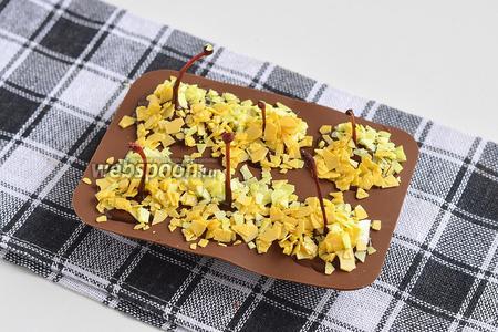 Сверху на ещё незастывший шоколад посыпать шоколадные хлопья со вкусом апельсина и лимона. Отправить формочку на 15 минут в морозильную камеру.