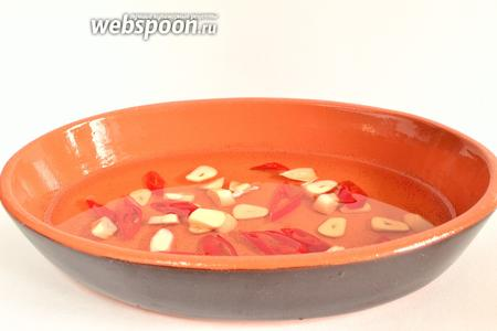 Налить в керамическую форму оливковое масло, добавить чеснок и перец чили и поставить в духовку на 10 минут, при 200°С. Надо нагреть масло, чтобы оно начало кипеть.