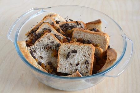 Пересыпьте хлеб нарубленным шоколадом и изюмом. Постарайтесь, чтобы кусочки шоколада и и изюм попали между ломтиками хлеба. Залейте все яично-молочной смесью. Оставьте на столе минут на 15, чтобы хлеб впитал жидкость.
