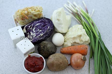 Возьмите такие продукты: капусту белокочанную и краснокочанную, лук, морковь, свёклу, масло подсолнечное, молодой чеснок перо, томатную пасту, яйца куриные, перец сладкий, картофель, воду, соль, перец молотый, лавровый лист.