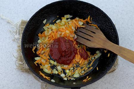 А пока обжарьте на подсолнечном масле мелко нарезанный лук и тёртую морковку до мягкого состояния. Добавьте томатную пасту и жарьте около 5 минут.