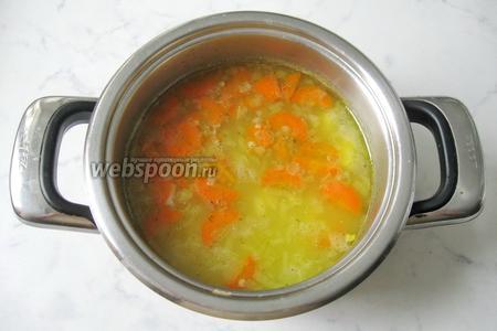 Добавить пшено и лук с морковью в кастрюлю с бульоном и картофелем. Положить лавровый лист, перец чёрный молотый, перец чёрный горошком и соль.