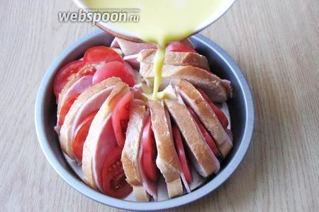 Смесь молока с яйцами вылить на ломтики батона с маслом, ветчиной и помидорами.