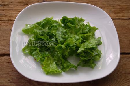 На порционную тарелку выложите немного листьев салата.