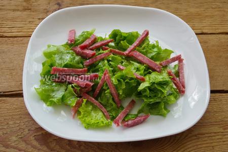 Колбасу салями нарезать соломкой. Выложить на салатные листья.