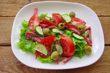 Разложите оливки. Полейте салат оставшейся заправкой.