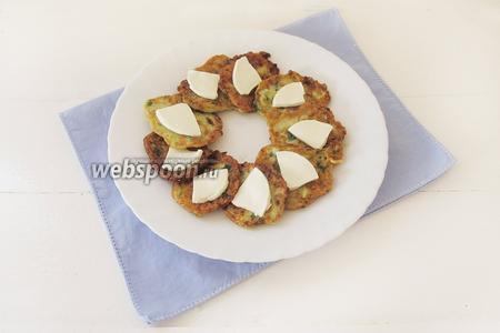 Положим сверху на оладушки кусочки мягкого сыра. Перед подачей блюдо можно украсить и посыпать рубленой петрушкой.