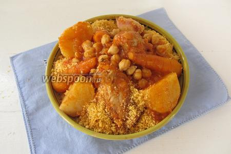 Кладём кус-кус в глубокую тарелку горкой и выкладываем сверху куски курицы и овощи. Дополнительно поливаем соусом. Блюдо готово.
