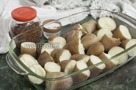 Отварим небольшой картофель в мундирах. Разломаем его на половинки и сложим в жаропрочное деко.