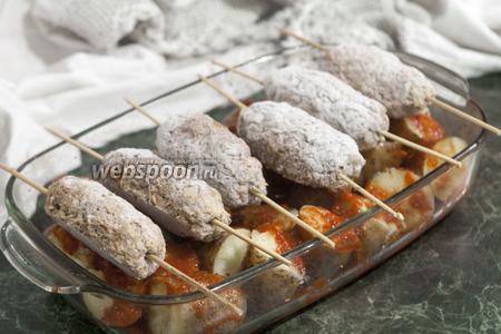 Поверх картофеля в соусе укладываем шпажки с кебабами. Отправляем блюдо в горячий духовой шкаф.