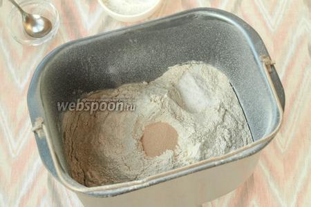 В центре сделать небольшое углубление и всыпать дрожжи. В один угол насыпать соль.