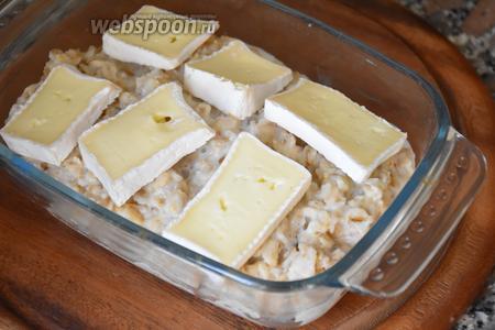 Кашу переложить в огнеупорную форму, сверху выложить кусочки сыра и запекать в разогретой до 200°C духовке 5 минут.