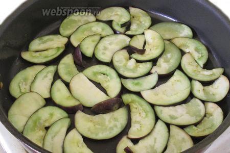 Подогреем сковороду, нальём растительного масла и выложим дольки баклажанов одним слоем.