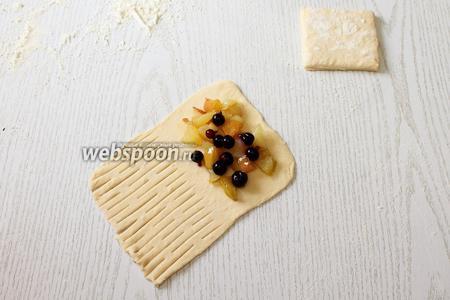 Выкладываем на тесто по 1 столовой ложке начинки. Посыпаем начинку ягодами чёрной смородины.