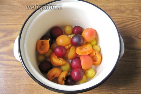 Выложить в кастрюлю алычу и абрикосы.