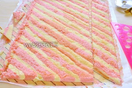По длинной стороне цветного бисквита вырезаем  диагональные полоски шириной 5 см, равной высоте торта, плюс 0,5 см (для выравнивания верха). Вырезаем первую диагональную полоску, обрезая торцевые стороны наискосок, чтобы аккуратно состыковать полоски по диагонали, прикладываем к торту и выравниваем.