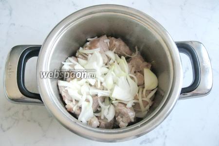 Добавить в кастрюлю со свининой нарезанный лук.