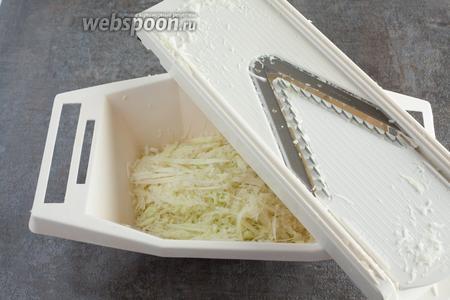 Капусту мелко-мелко трём на овощерезке на насадке, предназначенной для самой тонкой соломки — но не на тёрке для корейской моркови. Если капуста немолодая и горчит, эту стружку можно залить холодной водой, а потом слить воду через стальное сито.