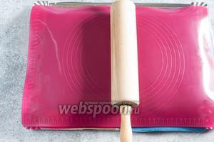 Снимаем с мастики один пласт силикона, переносим её на втором на торт, прокатываем скалкой поверх силикона, а потом его снимаем.