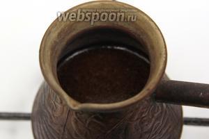 В турку положить 2 чайные ложки свежемолотого кофе и залить 1/2 частью воды. Довести до образования пенки.