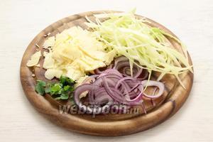 Тонкой длинной «лапшой» шинкуем сочную капусту, кольцами — лук лиловых сортов, мелко рубим зелень и почти прозрачными пластинами делим сыр.
